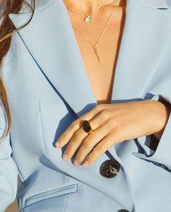 メンズライクなごつめのゴールドのシンプルなリングをつけた女性の手