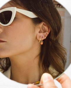 ナッツアンドコーヒーのシンプルなクラシックイアーカフゴールドを耳につけ鏡を見る人